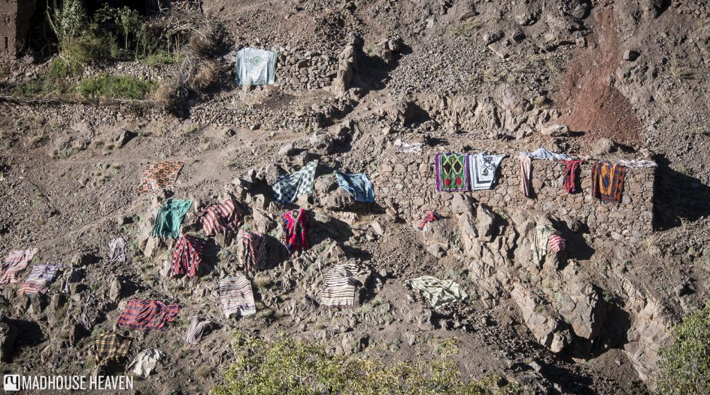 Washed carpets drying out on rocks on the side of the moutain - Hiking in the Atlas Mountains
