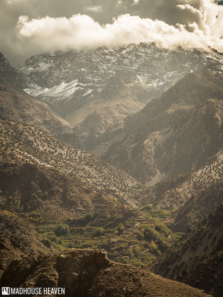 Billowing clouds over the Atlas Mountains as the sun sets over a Berber village