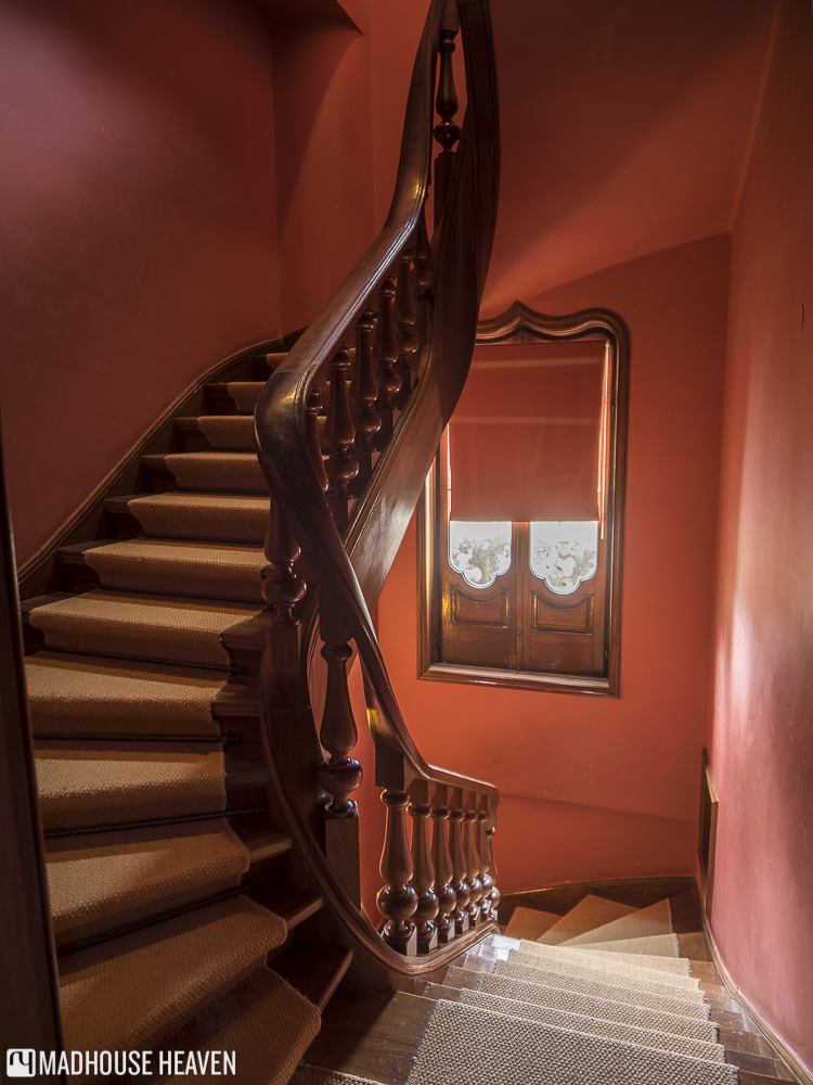 The beautiful chestnut main spiral staircase of Quinta da Regaleira complimented by deep red walls