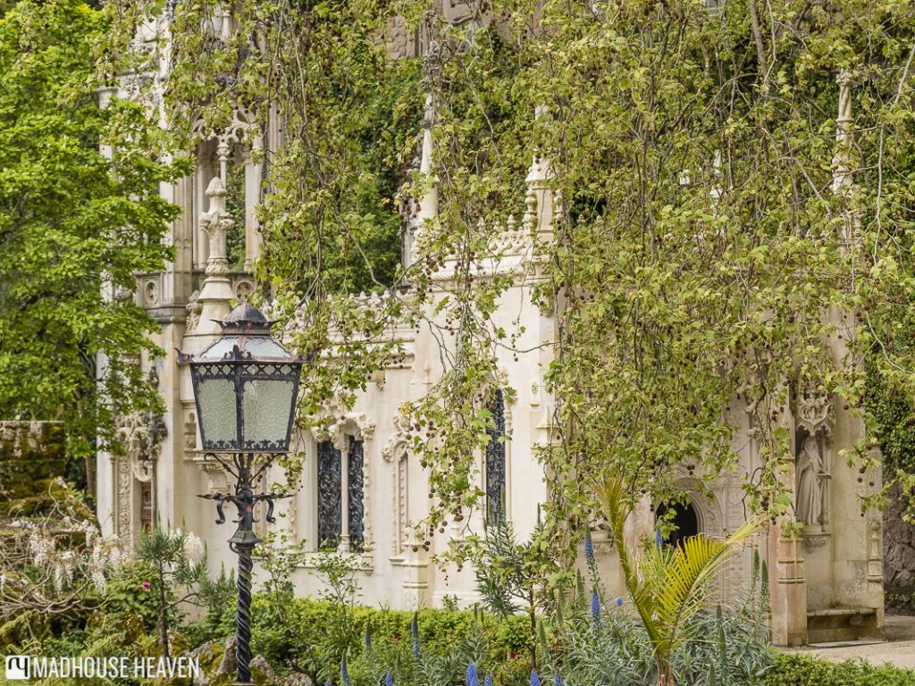 The Chapel of Quinta da Regaleira, elegantly decorated with floral motifs, hidden behind leaves and branches