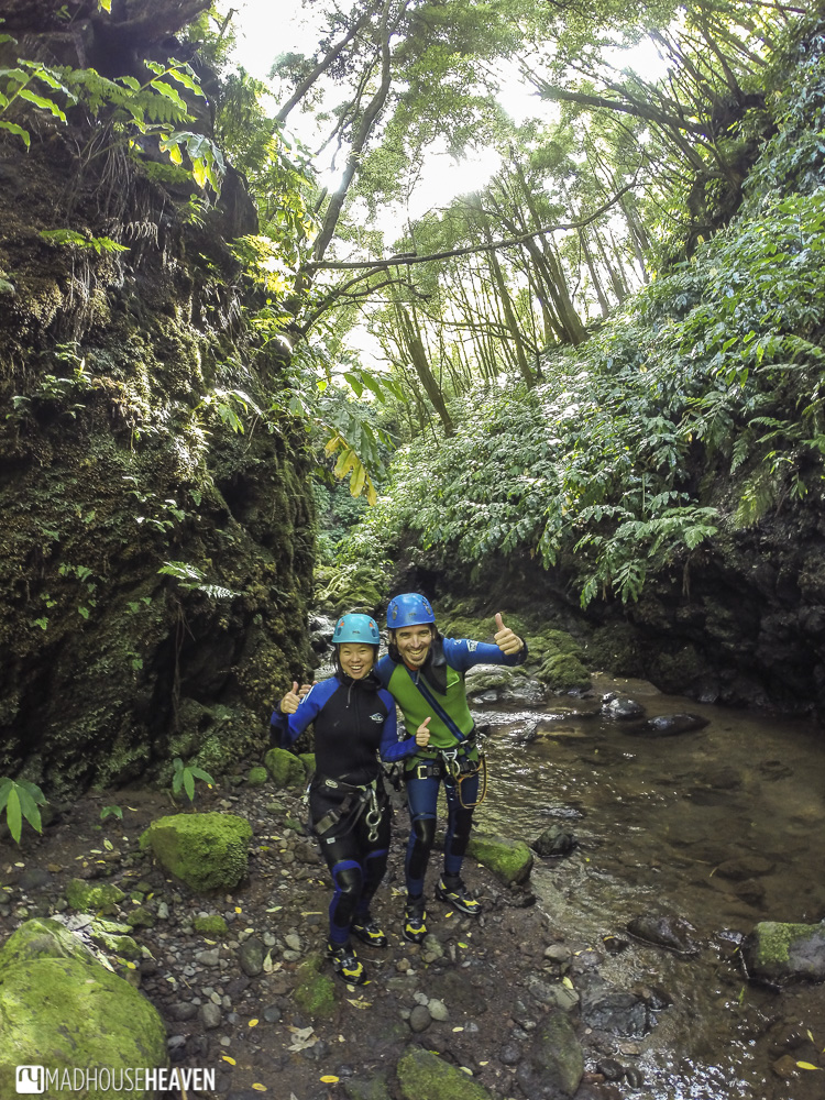Man and woman canyoning in a tropical canyon