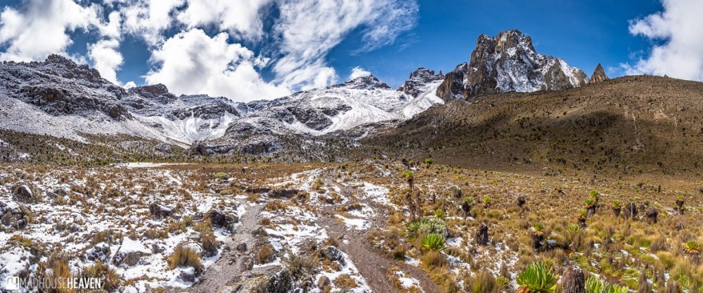 Panorama of a valley with the snow covered peaks of Mount Kenya in the back