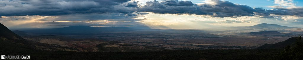 Panorama of the Great Rift Valley in Kenya, with an intricate interplay of light and shadows over its vast expanse