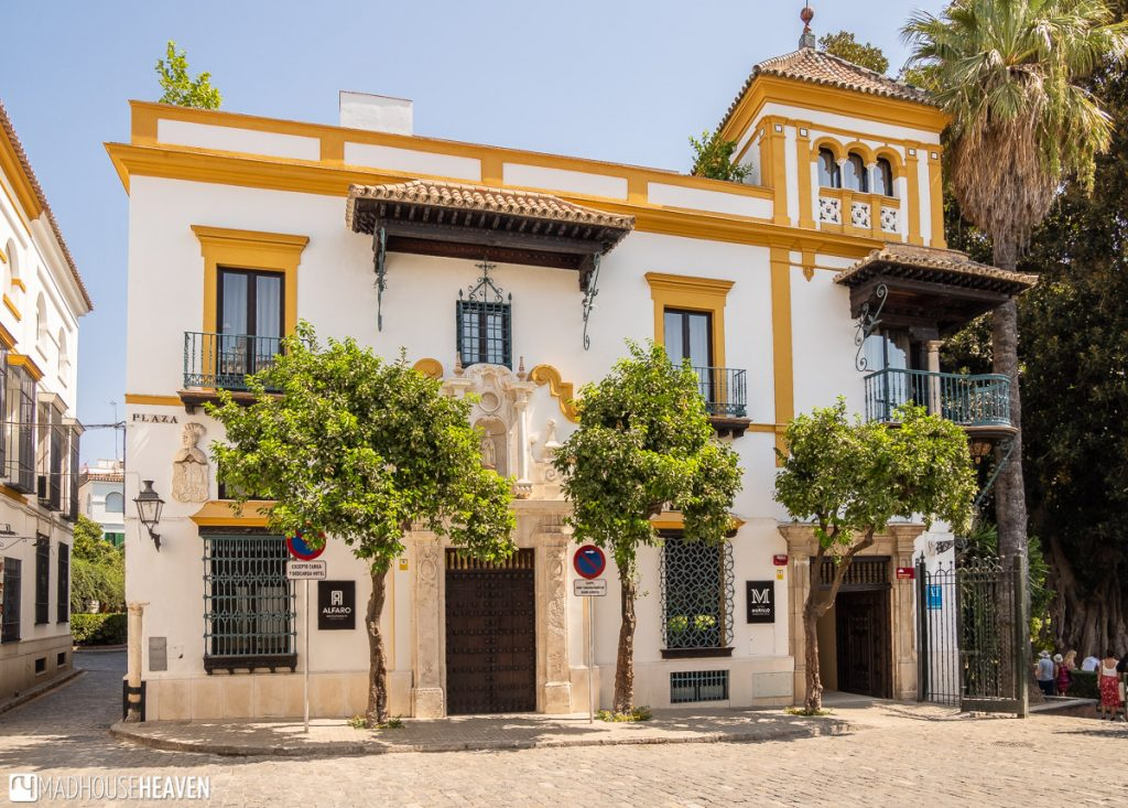 The balcony of Rosina, hanging of a white Renaissance styled building with three Seville orange trees in front
