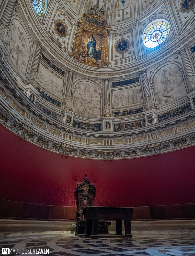 The majestic Renaissance interior of the Chapterhouse is empty save for a grand chair and a richly ornamented painting of the virgin Mary