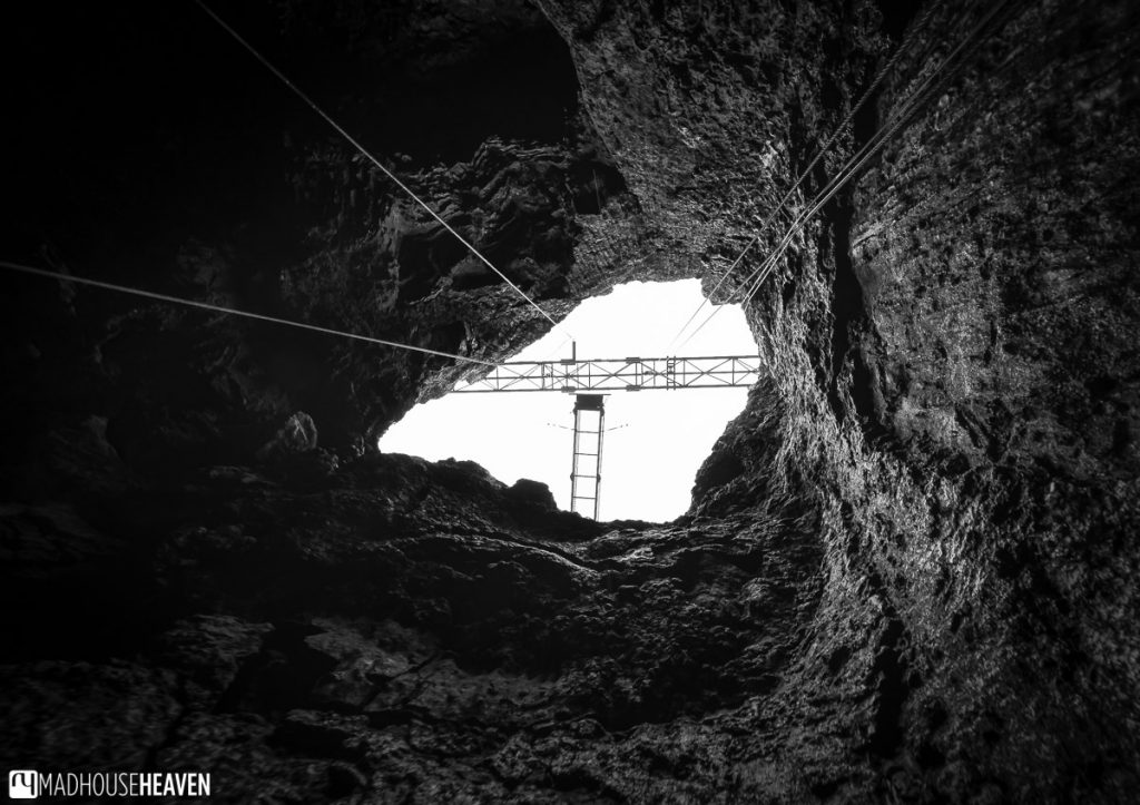 Black and white image of the final, narrowest point of the ascent, with the elevator's construction seen above the opening
