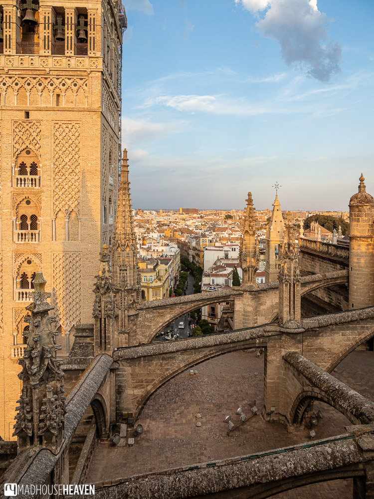 The view of the flat roof of the Seville Cathedral, flying buttresses, Gothic spires and the Giralda Tower,