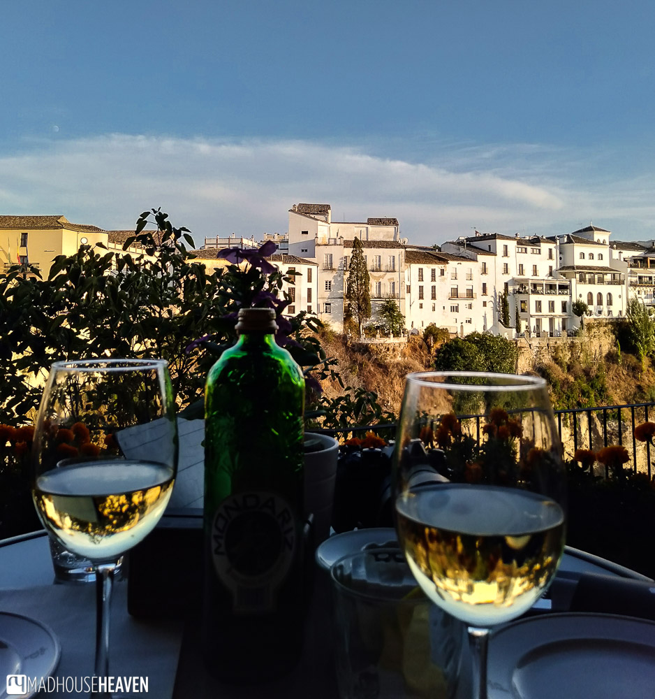 Glass of cava and some tapas, with a view of the Ronda old town across the El Tajo gorge