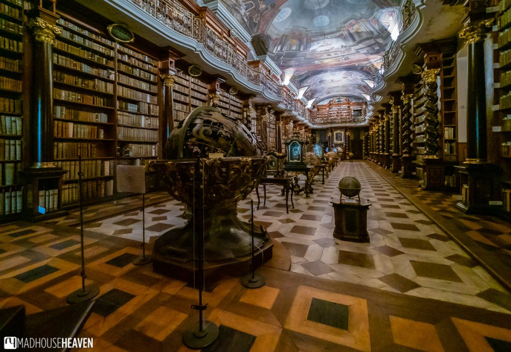 A wide angle view of the interior of the Klementinum Library, with its dark wood shelves and painted ceiling