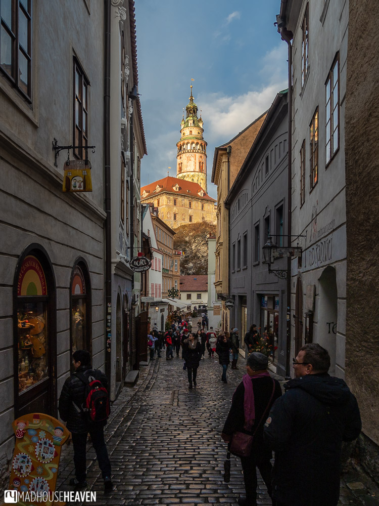 Sunlight hits the Cesky Krumlov castle tower, viewed from a narrow cobblestone street in the old town