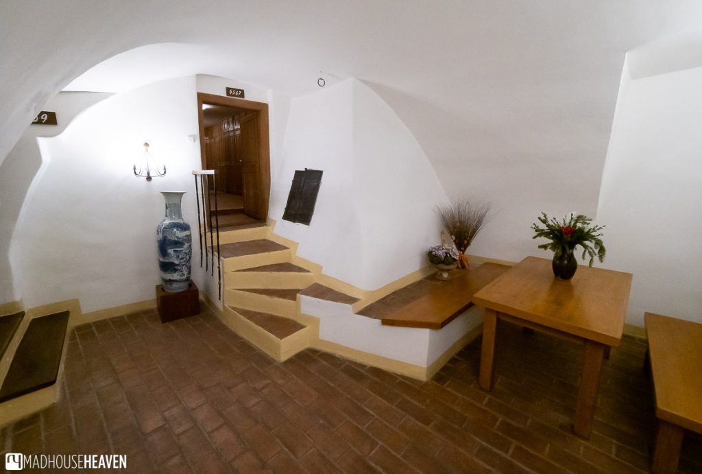 Low arched ceilings in a Gothic residential building in the Czech Republic. A short flight of stairs connect the interior of one building to the next.