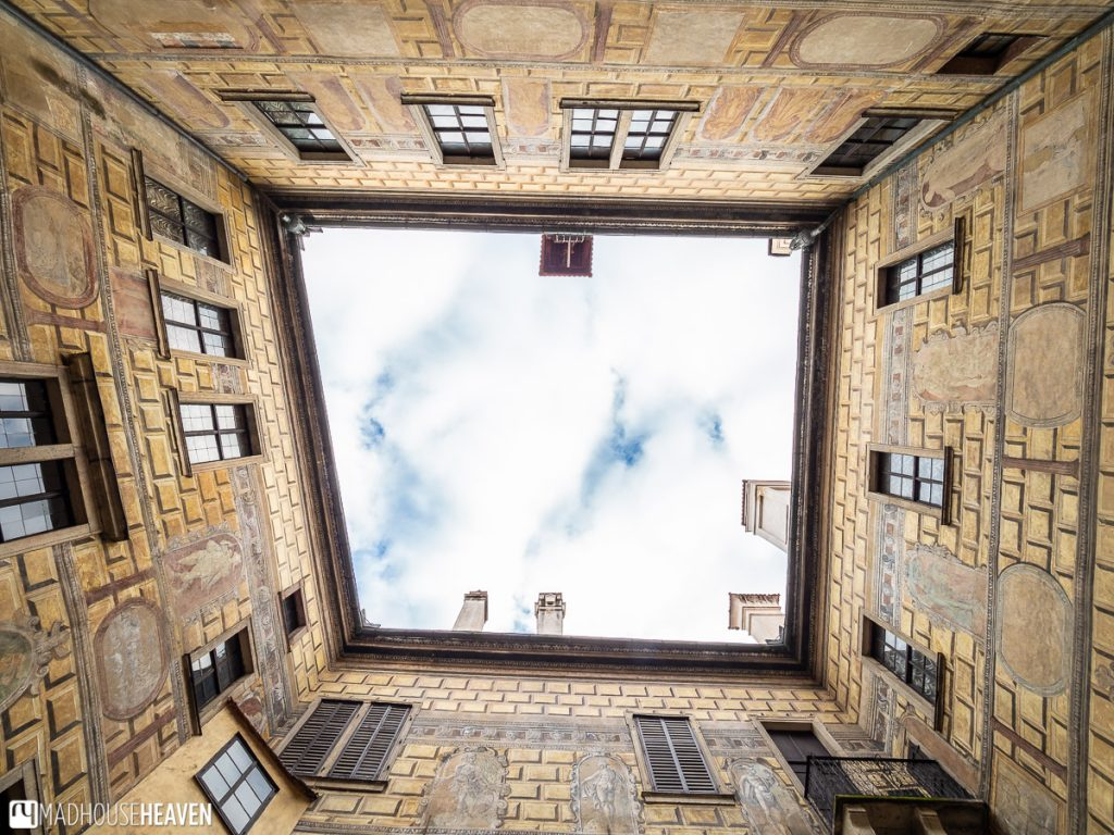 Cesky Krumlov's Castle Courtyard III as seen from below, opening up to a cloud covered patch of sky