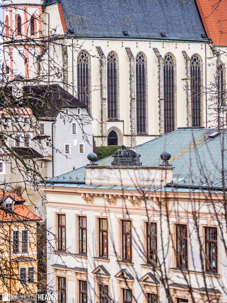 The Gothic windows of St. Vitus Cathedral in Cesky Krumlov, with restored Renaissance buildings in front
