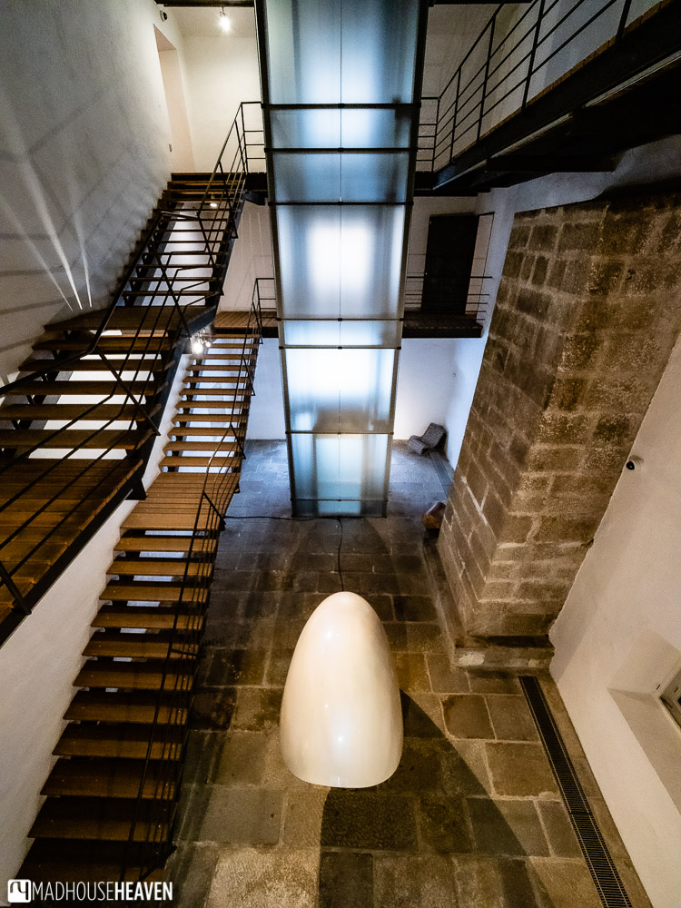Contemporary architecture interior with stone walls and free standing wooden staircases that span many floors