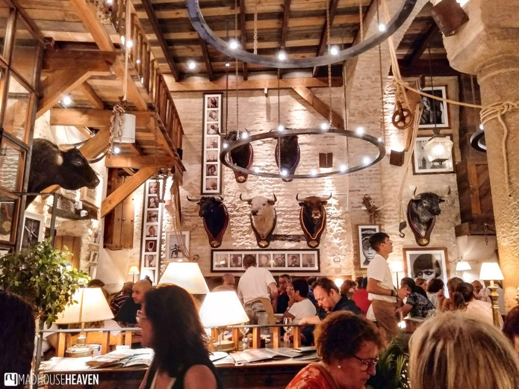 A restaurant in a Spanish country house featuring bull heads as trophies on the walls
