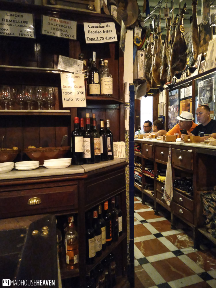 Interior of a typical Andalucian tapas bar with antique furniture and many bottles of wine