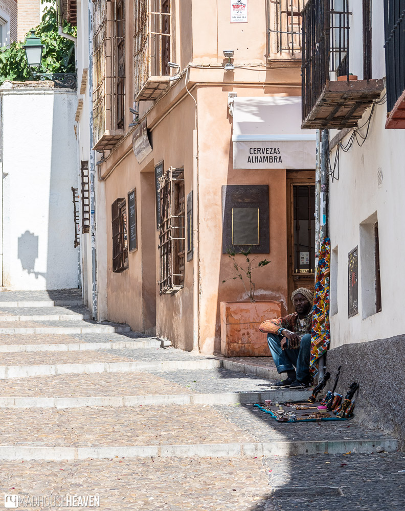A black vendor with a turban sitting on the cobblestone street selling craft to tourists
