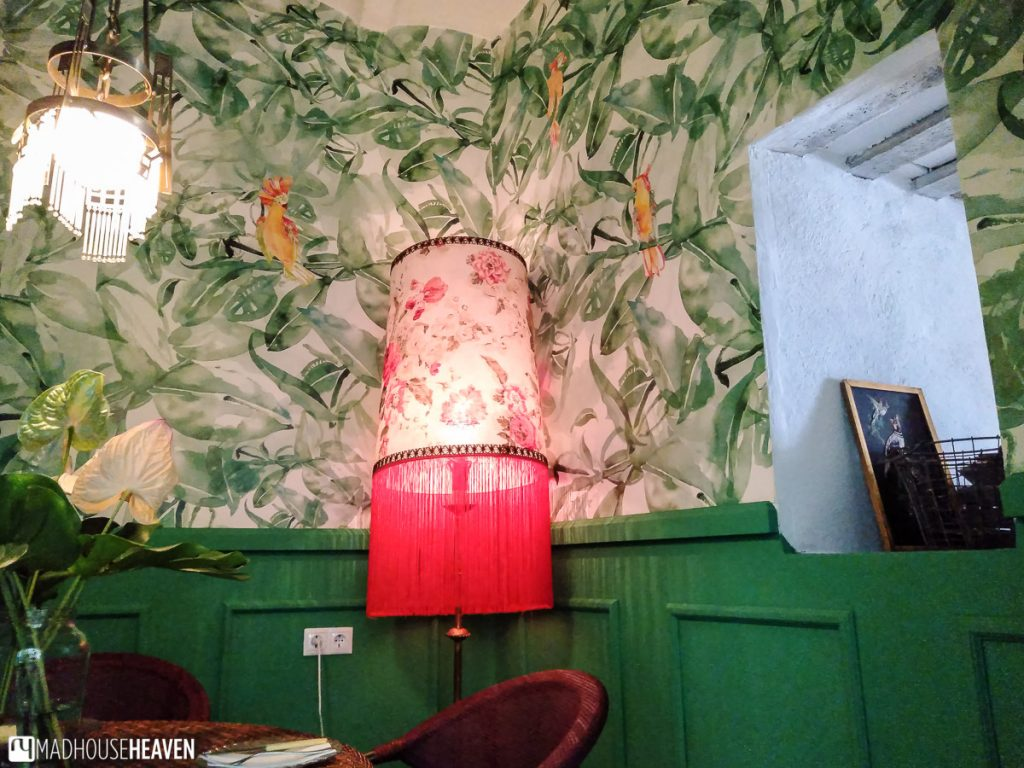 A themed restaurant room with green wallpaper and a bordello style lightshade
