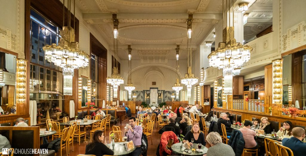 The brightly lit interior of the Municipal House café