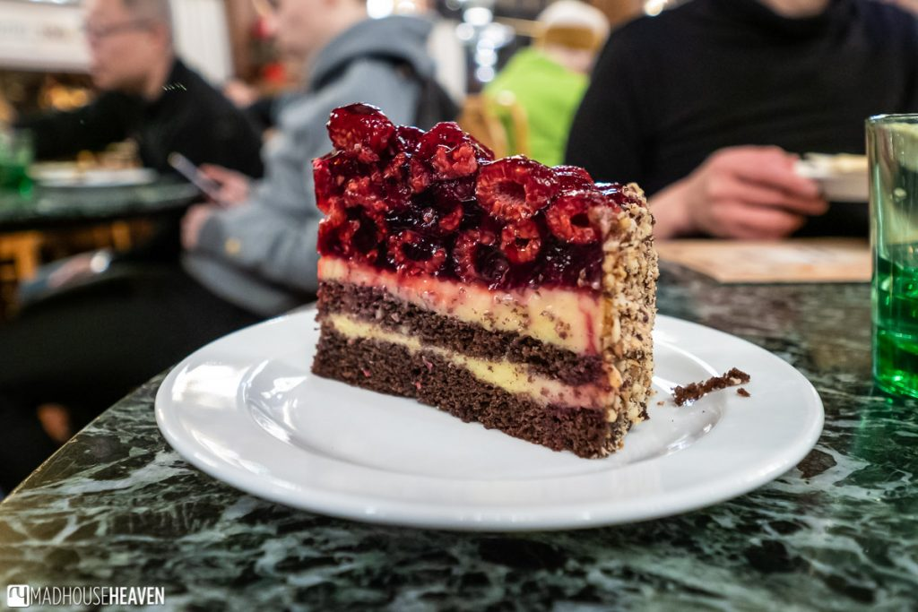 A chocolate cake topped with lots of raspberries and filled with cream